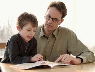 child reading with father